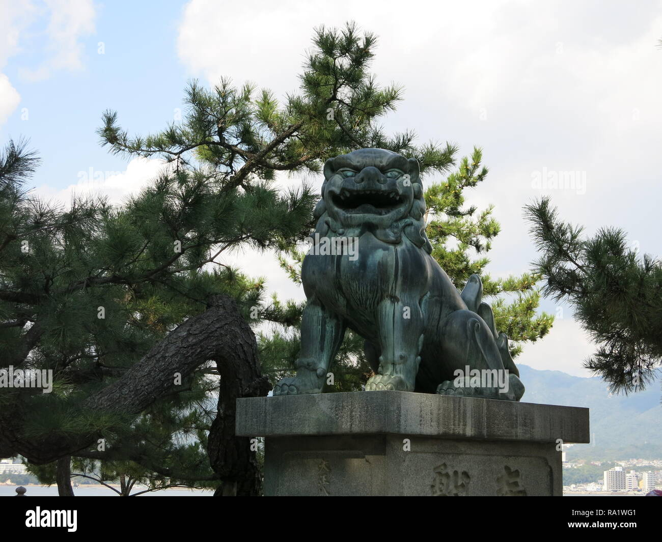 Close-up of the open-mouthed lion (agyoo), one of the pair of statues guarding the entrance to the Itsukushima Shrine, Miyajima island, Japan - Stock Image