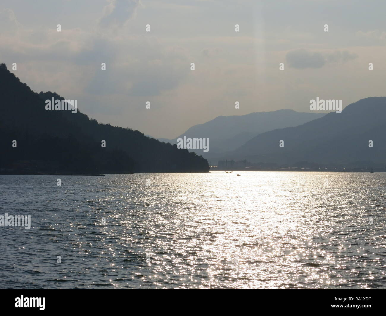 Romantic view of dappled water and distant hills whilst sailing across the Seto Inland Sea from Miyajima Island to Hiroshima, Japan - Stock Image