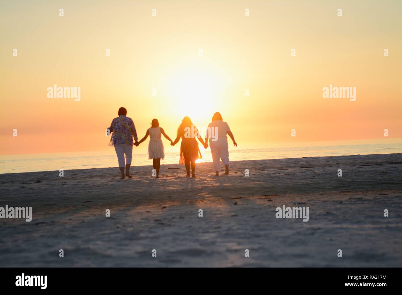 Happy Loving Family Holding Hands and Embracing While Facing the Bright Orange Yellow Sunset over the Ocean at the Florida Beach Horizon Stock Photo