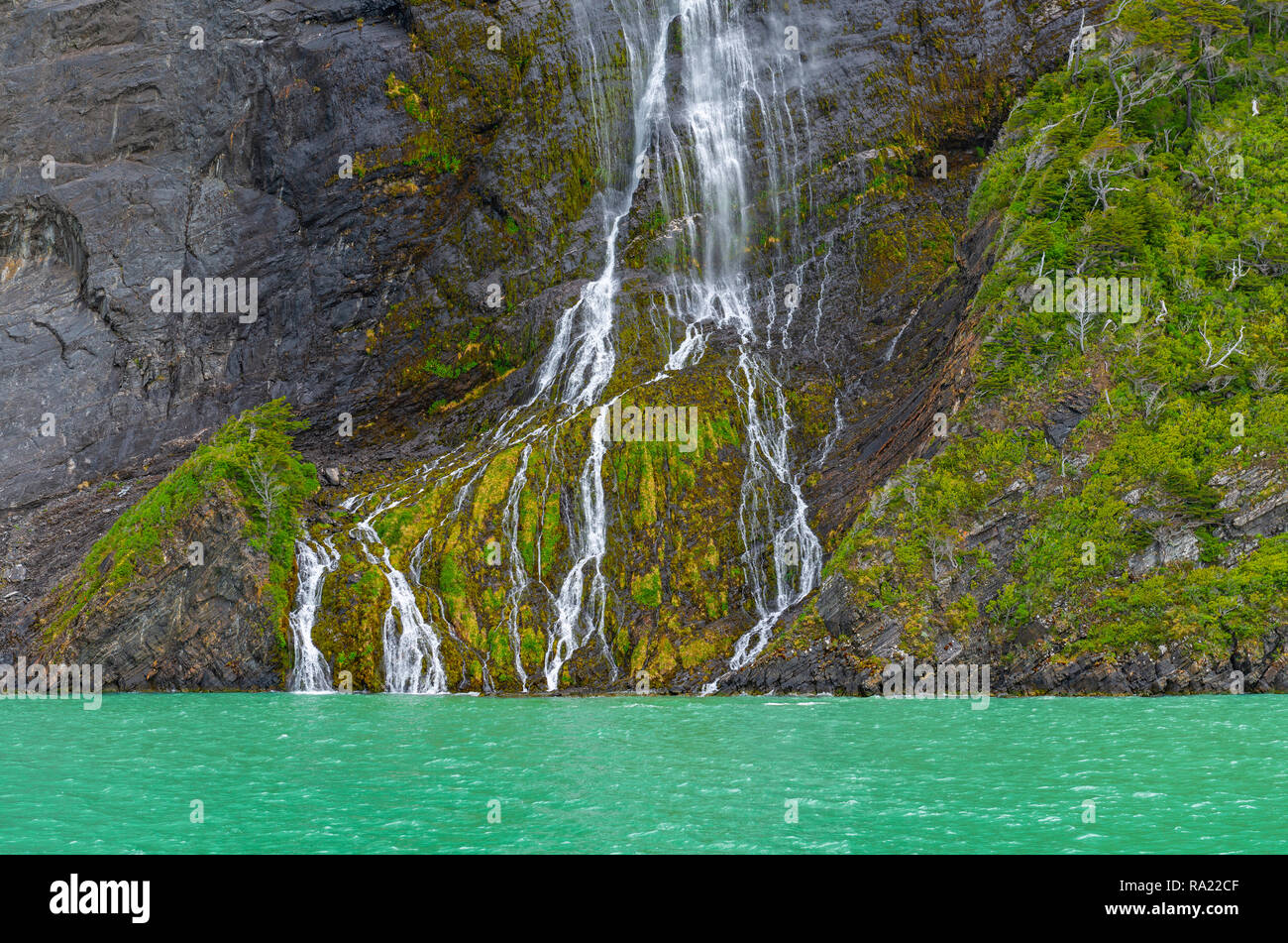 A wonderful waterfall along a cliff inside the Bernardo O'Higgins National Park near Puerto Natales, Patagonia, Chile. - Stock Image