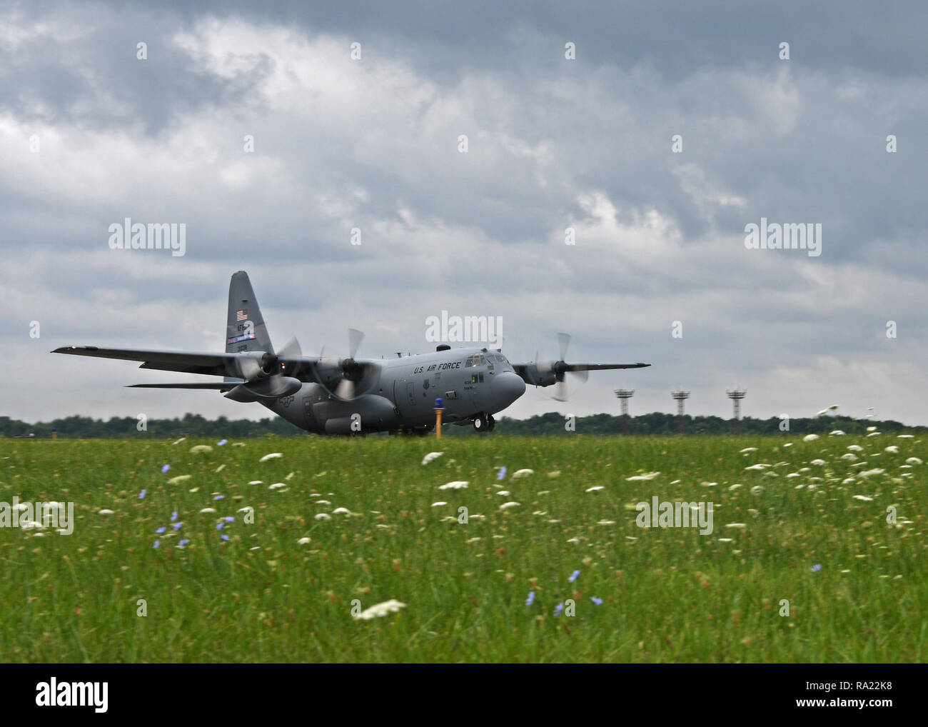 A C-130 Hercules aircraft from the 94th Airlift Wing performs a touch and go at Youngstown Air Reserve Station, August 8, 2018. During touch and goes, the aircraft descends to the runway, lands, and then takes back off again. This is done to help simulate tactical operations. (U.S. Air Force photo by Staff Sgt. Miles Wilson) - Stock Image