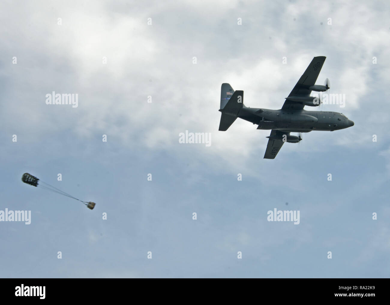 A C-130 Hercules aircraft from the 94th Airlift Wing conducts an Airdrop at Youngstown Air Reserve Station, August 9, 2018. The airdrop was part of a drop competition that the 908th Aerial Squadron, 700th AS, and 757th AS took part in during Tac Week. (U.S. Air Force photo by Staff Sgt. Miles Wilson) - Stock Image