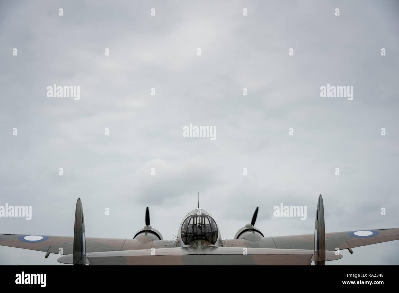 Wide rear view of WWII two engine bomber against a dark cloudy sky - Stock Image