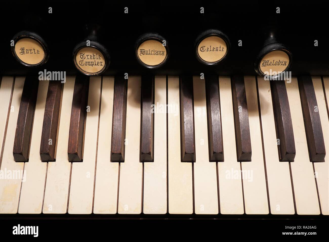 Close up of the keys and stops of an old pump organ - Stock Image