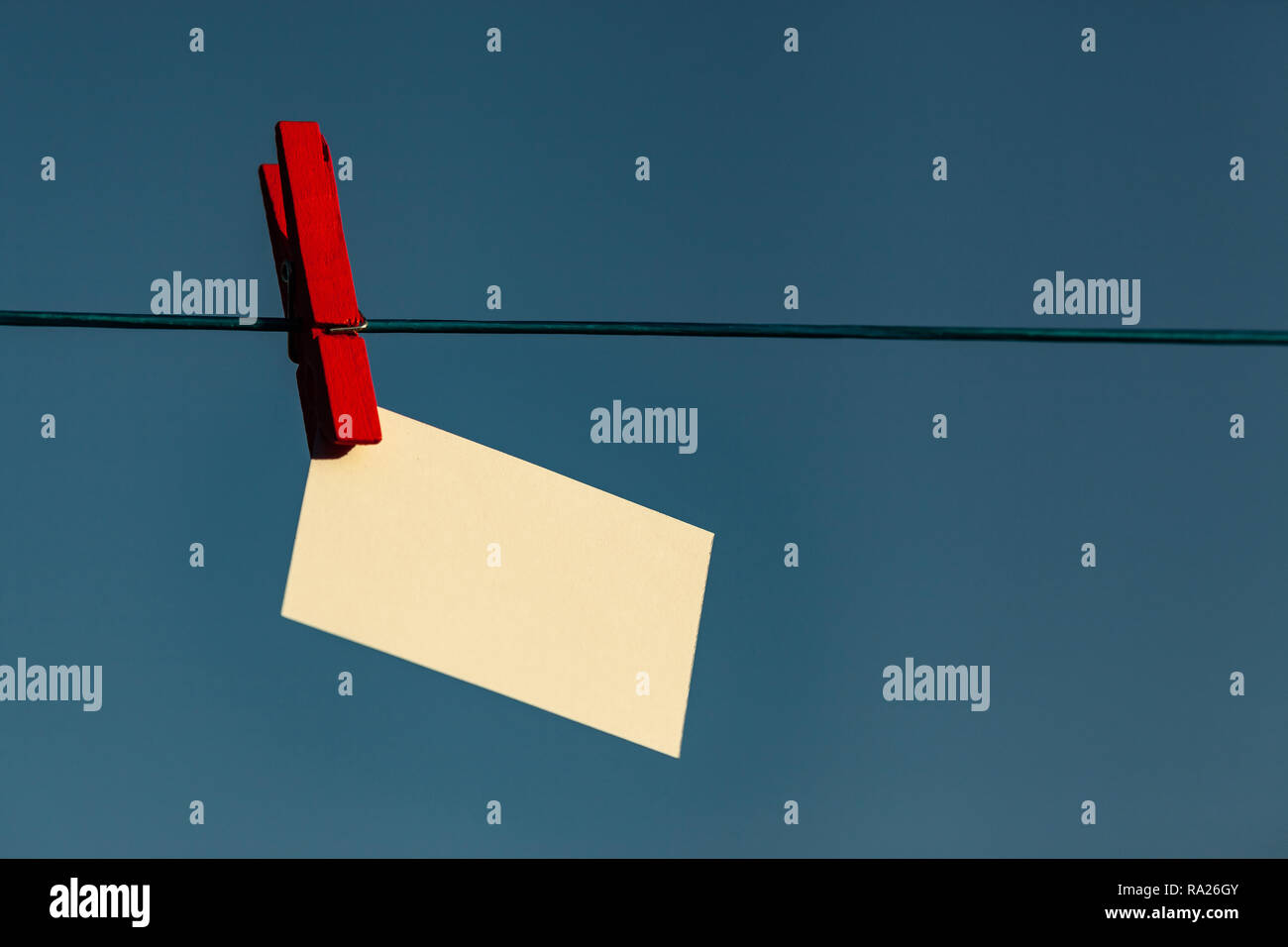 Red peg and a card on a washing line - Stock Image