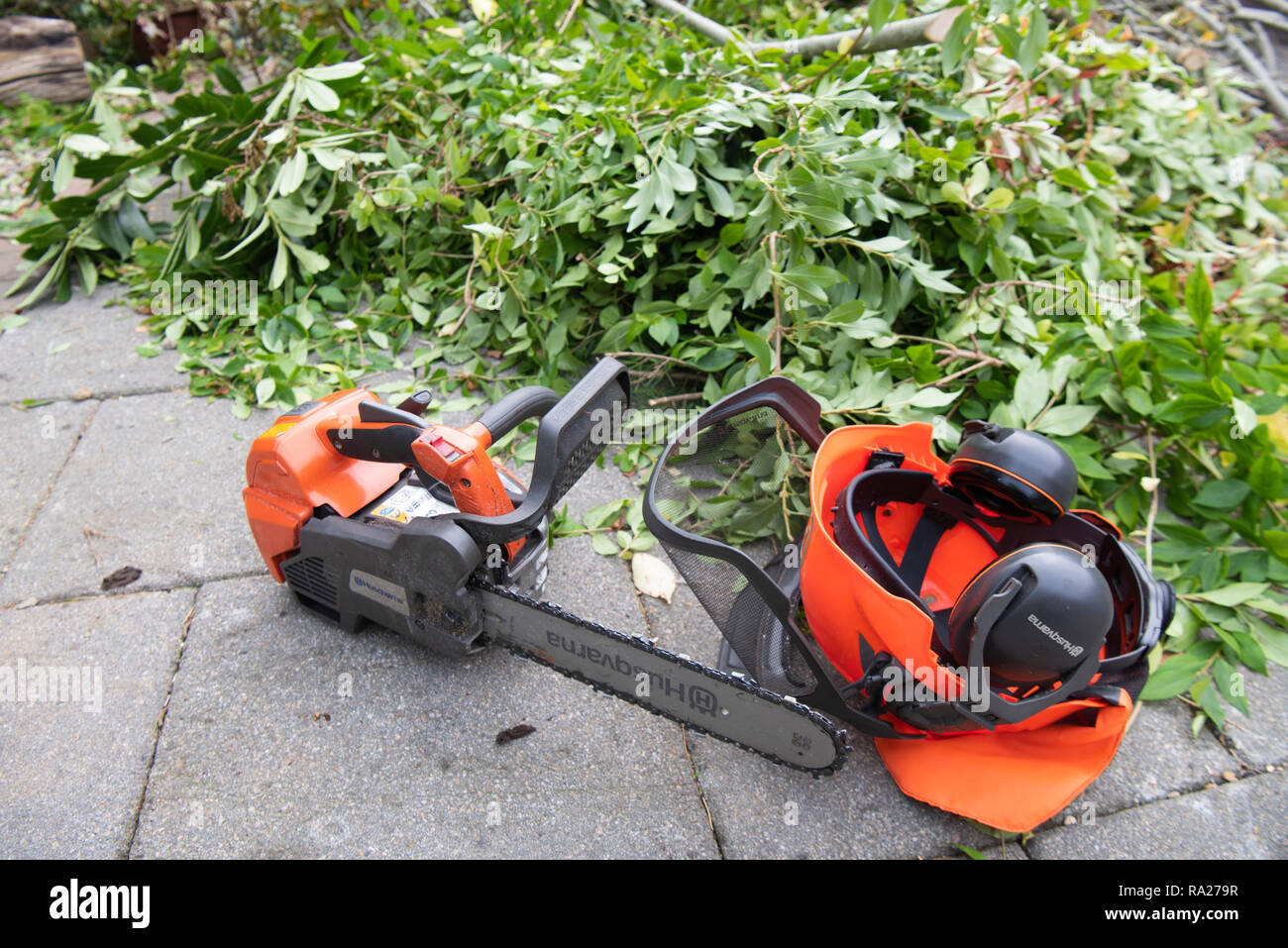 Husqvarna chainsaw and helmet with ear defenders lying on a patio beside branches which have just been cut down. - Stock Image