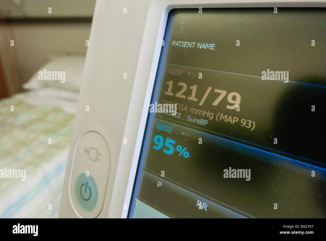 WelchAllyn blood pressure monitor in a hospital ward showing a normal blood pressure of 121/79, and a blood saturation level of 95%. - Stock Image