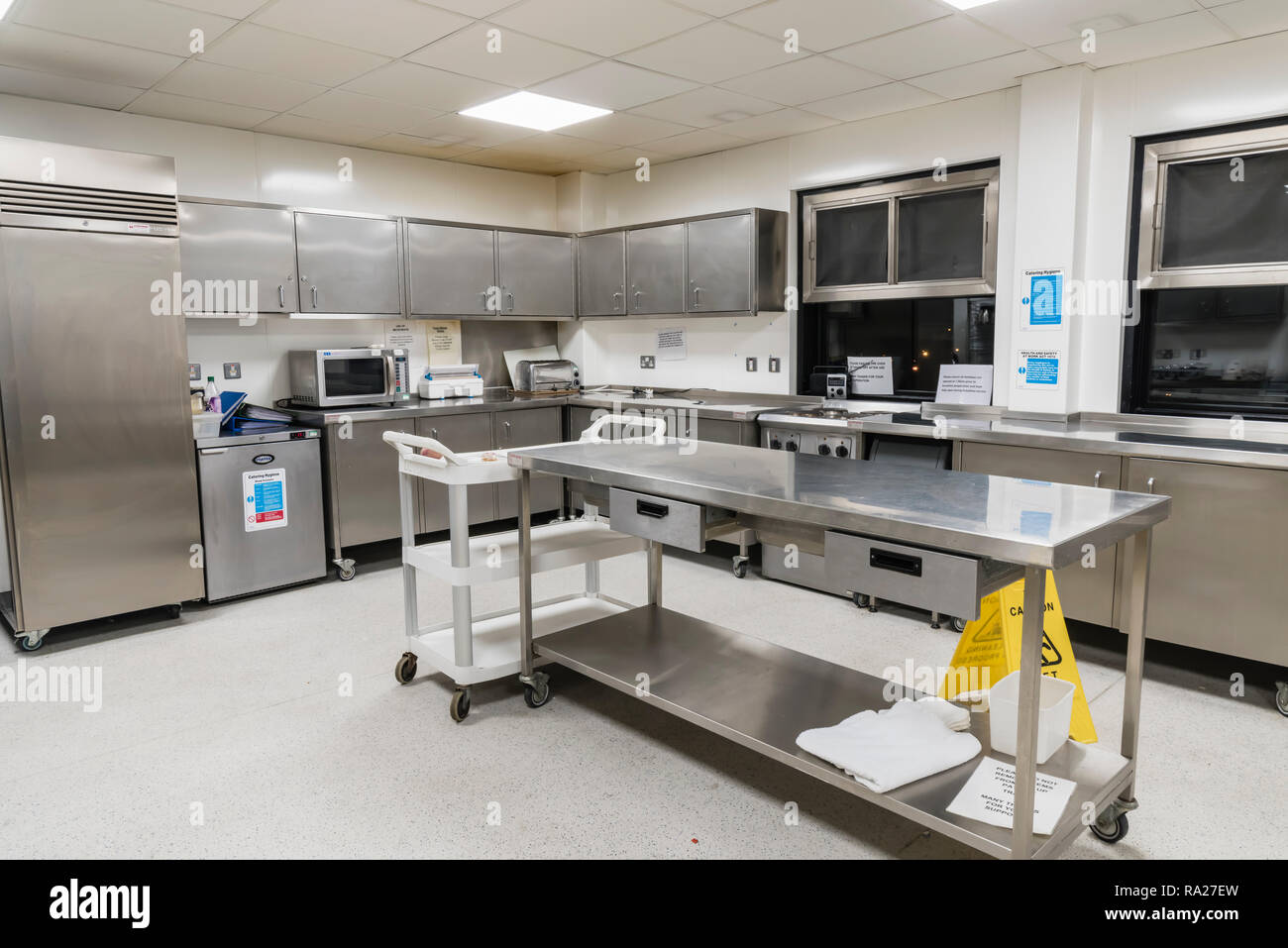 Stainless steel cupboards and worktops in the kitchen of a hospital ward stock image