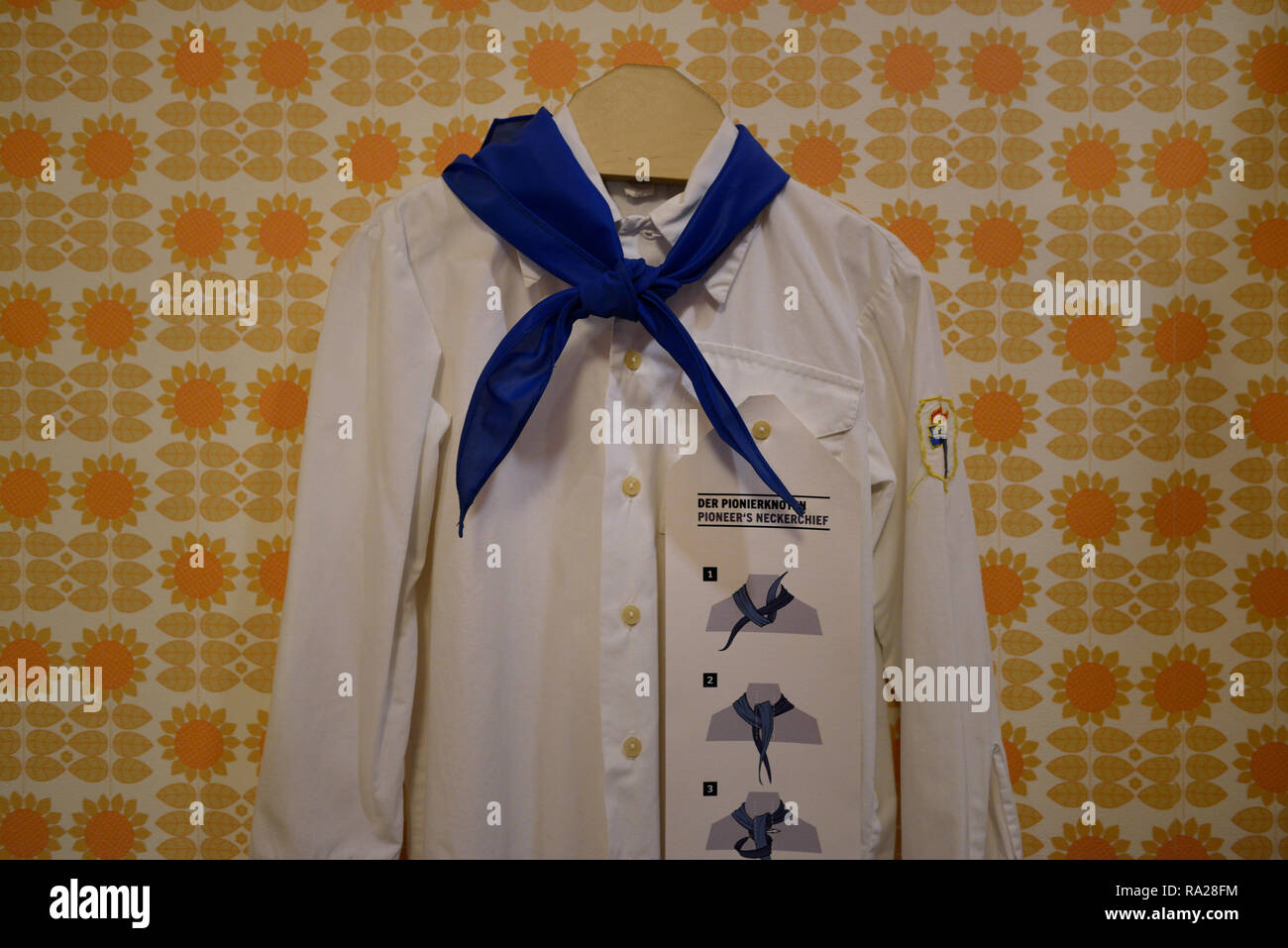 Uniform of the Ernst Thälmann Pioneer Organisation from the former GDR consisting the white short & the blue triangular necktie. DDR museum, Berlin. - Stock Image