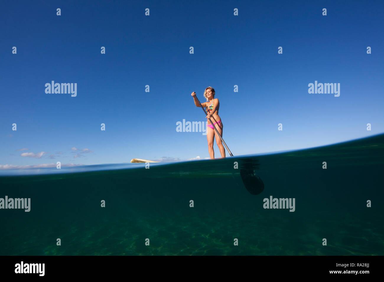 Split level view of a woman stand up paddling at Palauea, Maui, Hawaii. - Stock Image