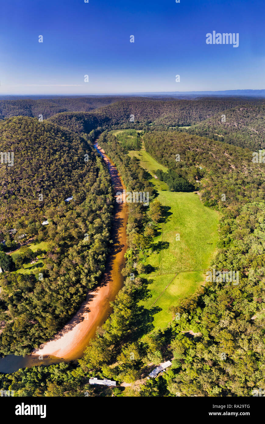Overhead top down view over river stream of Colo River around Colo Heights area of the Gread Dividing range in Australia in vertical panorama under bl - Stock Image