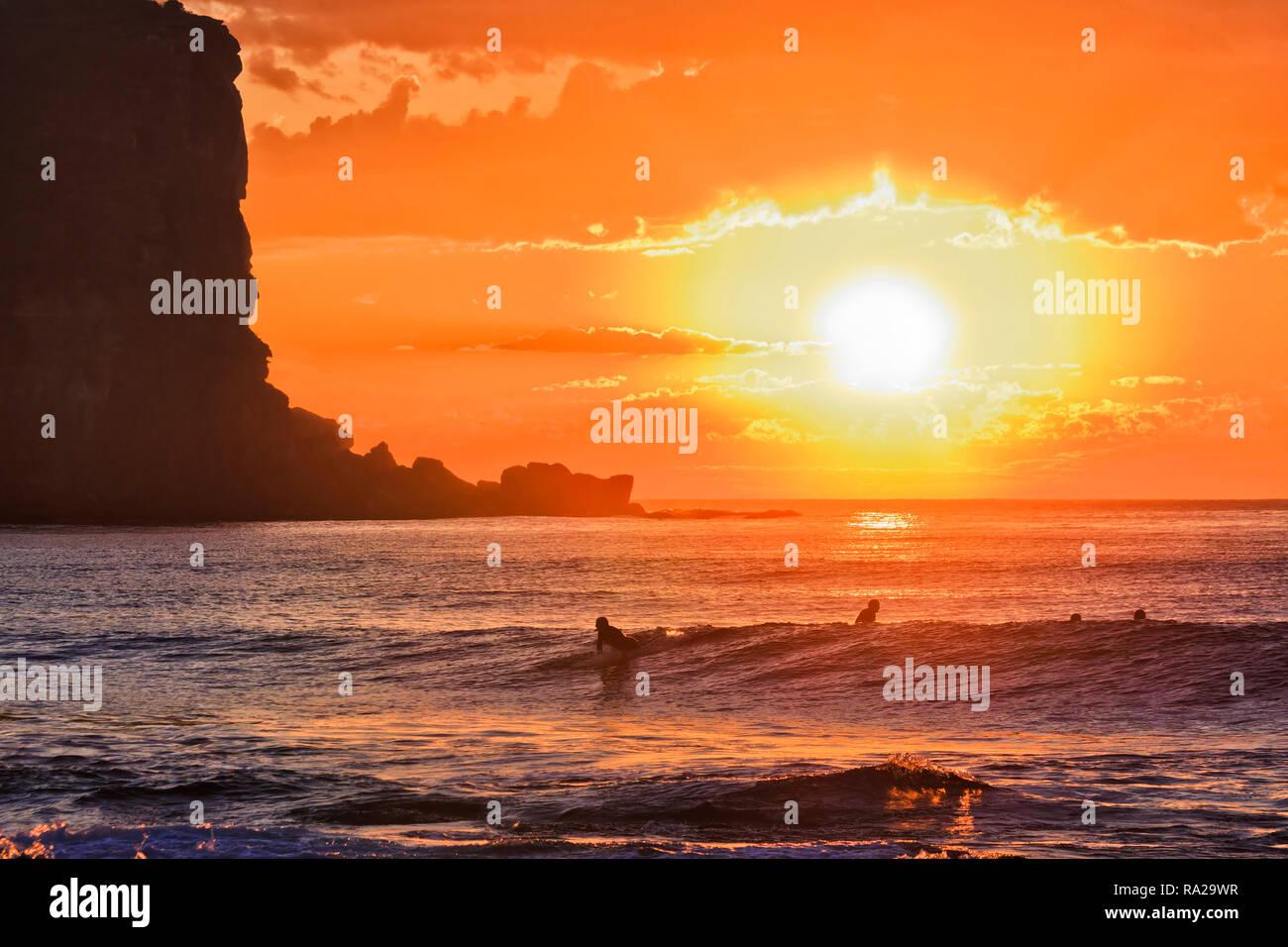Bloody orange sun over sea horizon flooding rolling waves with windsurfers off Avalon beach in Australia Sydney Northern beaches on Pacific coast. - Stock Image