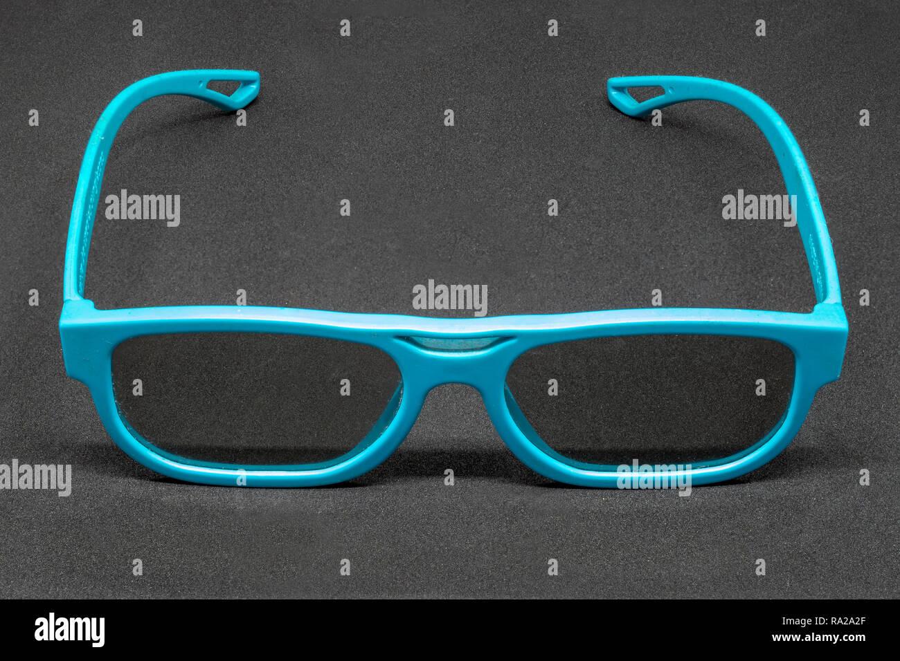 Light Blue 3 Dimensional glasses on a dark grey background - Stock Image