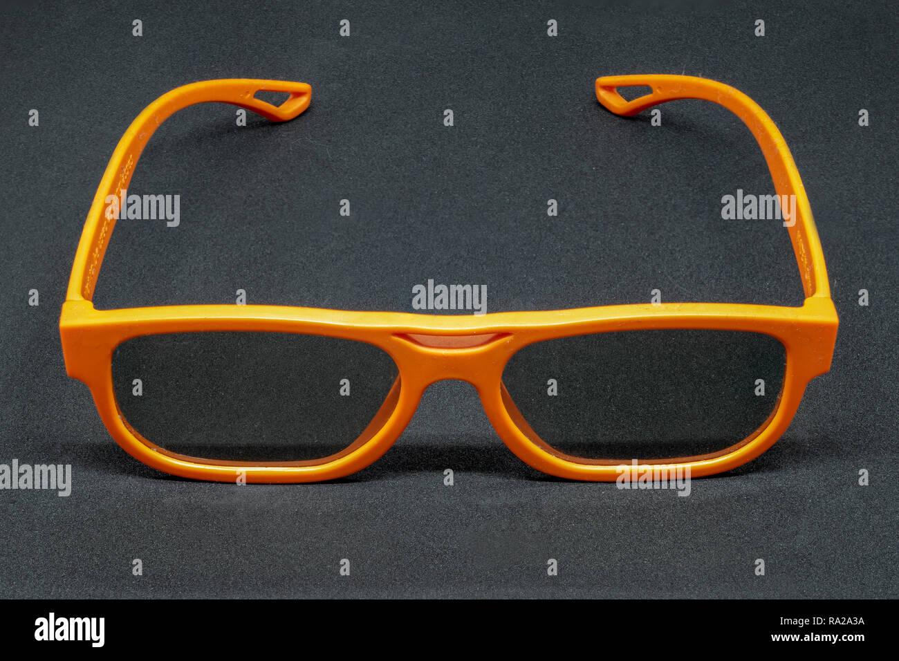 Orange 3 Dimensional glasses on a dark grey background - Stock Image