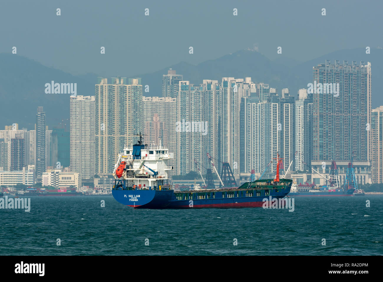 The Panamanian flagged general cargo vessel 'PL Hau Laam' moored off Tai Kok Tsui in Hong Kong with towering apartment blocks fringing the harbour. - Stock Image