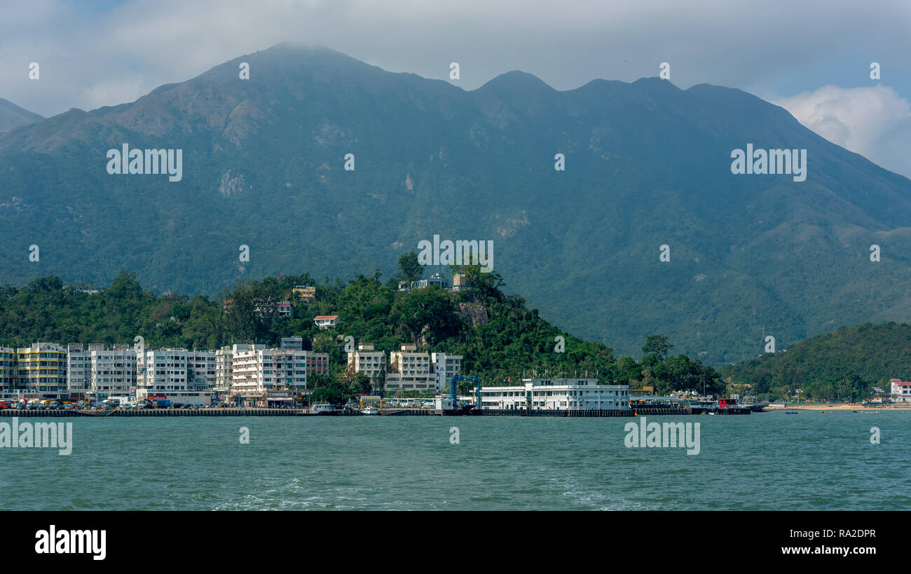 Low rise apartments line the waterfront up to the Silvermine Bay Ferry pier on Mui Wo, Lantau with the majestic Sunset Peak as a backdrop. - Stock Image