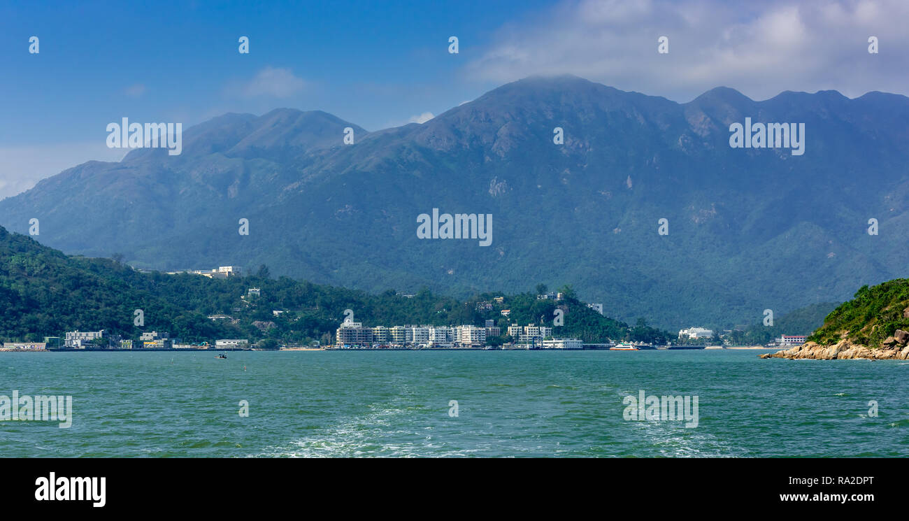 The twin peaks of Lantau Island, Sunset and Lantau Peaks dominate the low rise apartments lining the shore of Silvermine Bay. - Stock Image