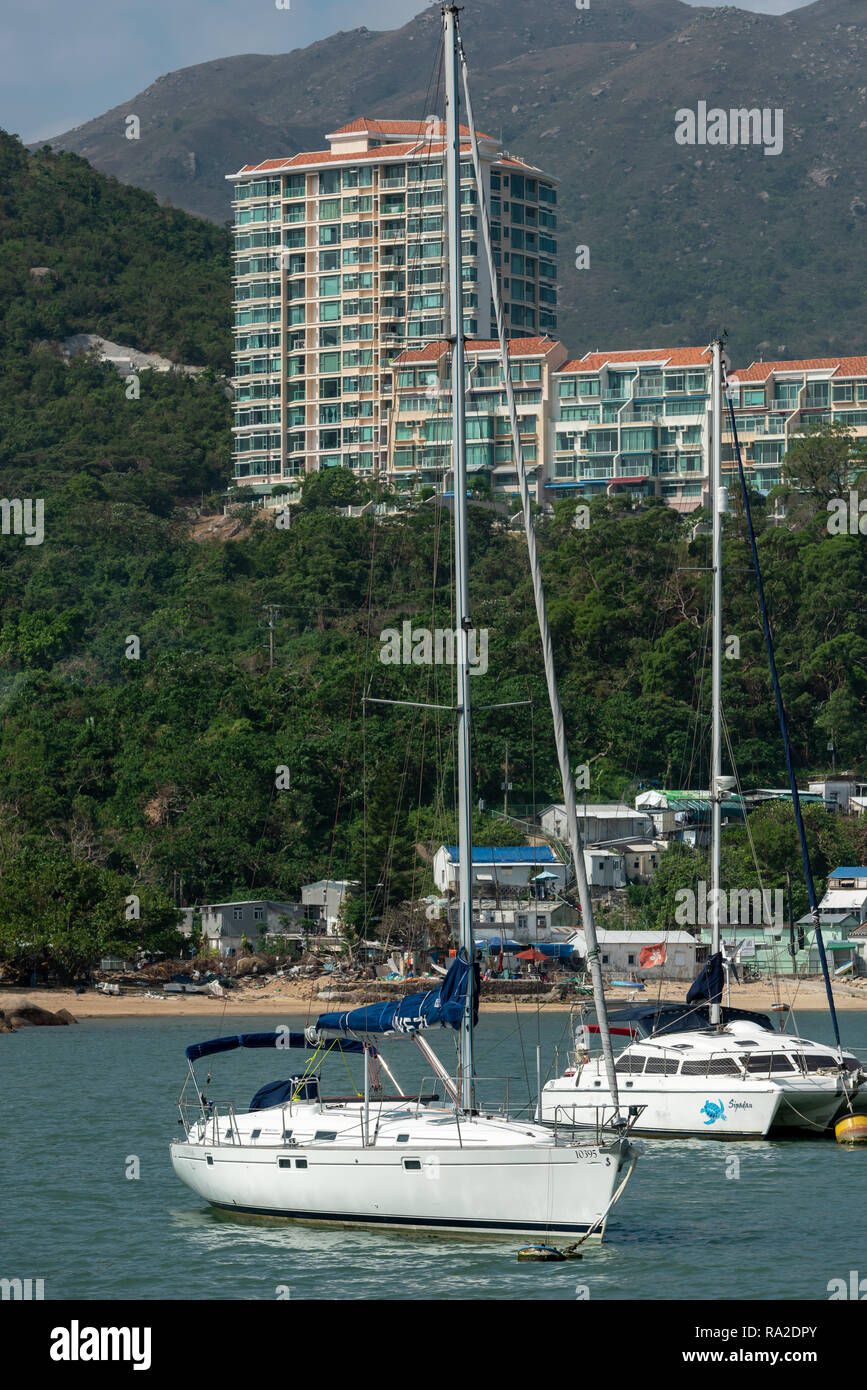 Discovery Bay contrasts: tin shacks line the beach, expensive yachts moored in the bay, and luxury apartments command the hillside - Stock Image