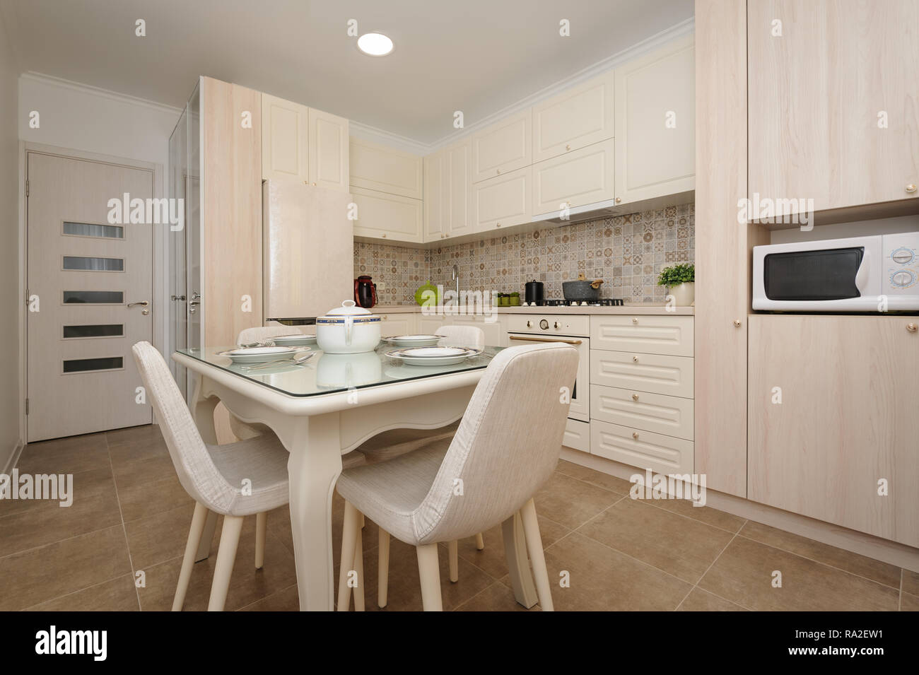 Salle A Manger Americaine modern beige colored kitchen and dining room stock photo