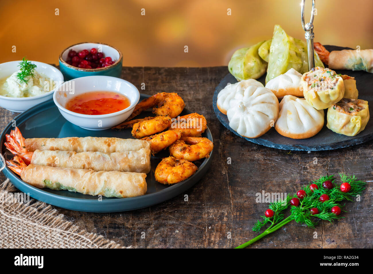 Giant king prawns and selection of mini Chinese dumplings with sweet chili and yogurt dipping sauces. Party food idea. Stock Photo