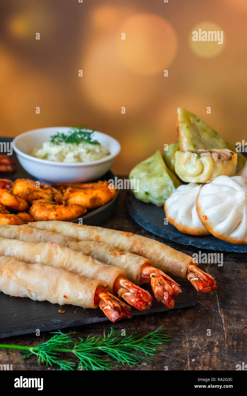 Giant king prawns and selection of mini Chinese dumplings with yogurt dipping sauces. Party food idea. Stock Photo
