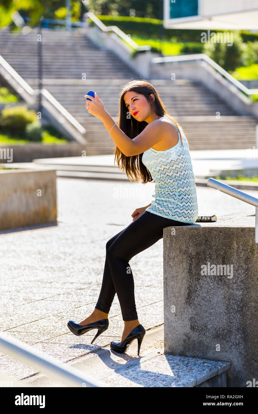 Standing outside looking at handy small mirror fixing hand-brushing long brunette hair attractive young woman 20s twenties Black tight pants - Stock Image