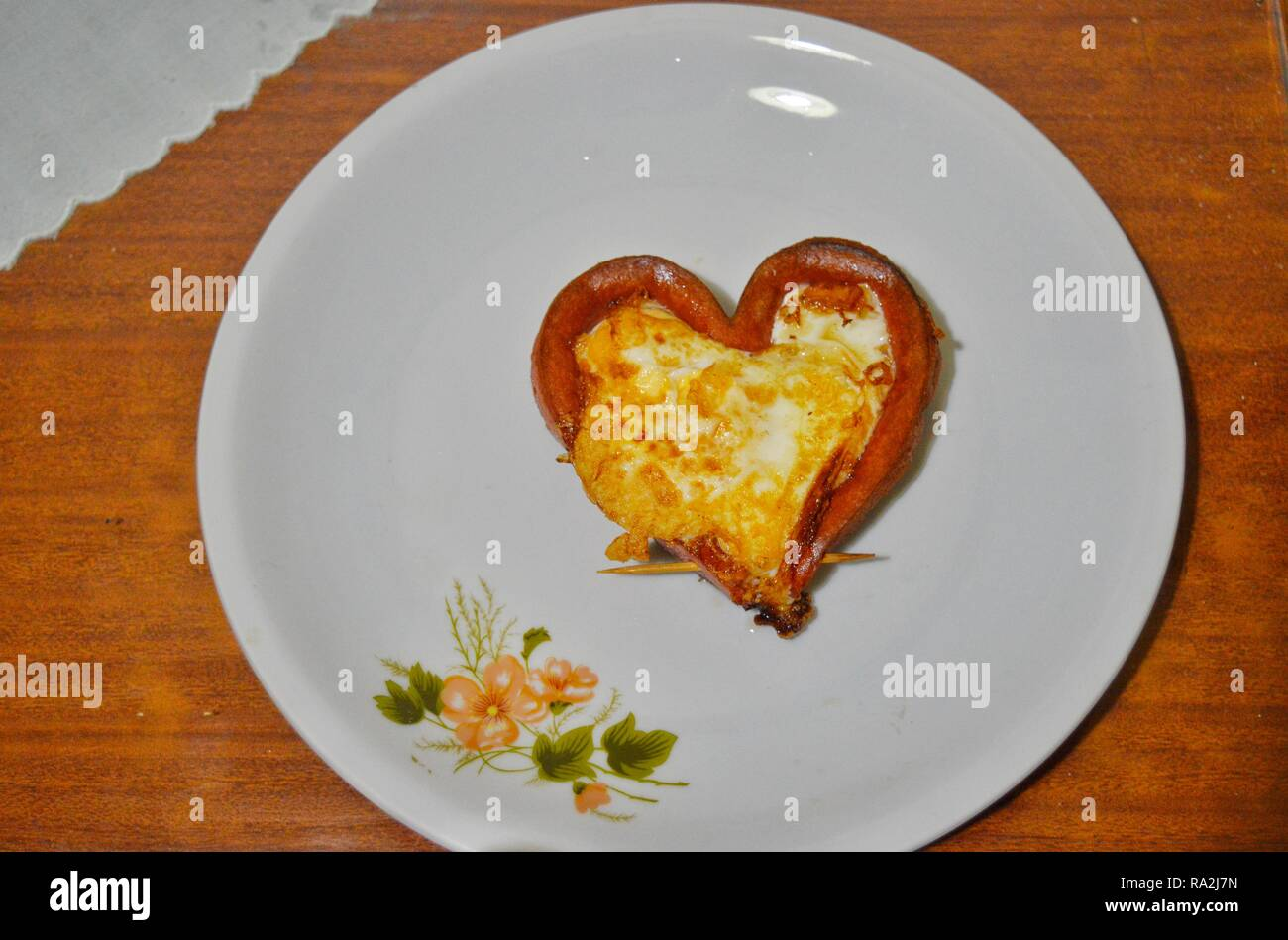 Heart shaped meal of eggs and a hot dog on a white plate - Stock Image