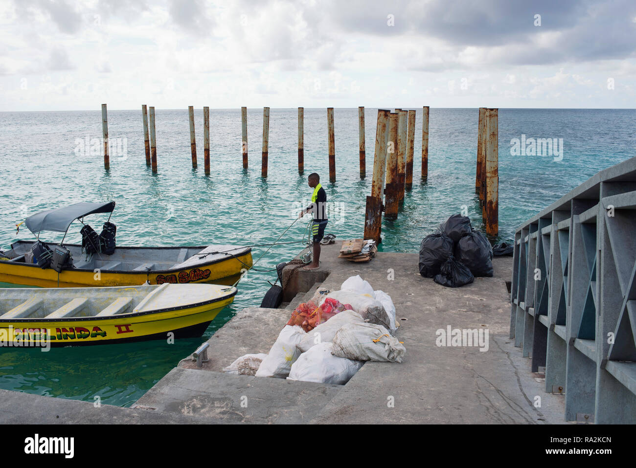 Behind the scenes of a popular seaside destination: local man working on taking away rubbish bags. Johnny Cay, San Andrés island, Colombia. Oct 2018 - Stock Image