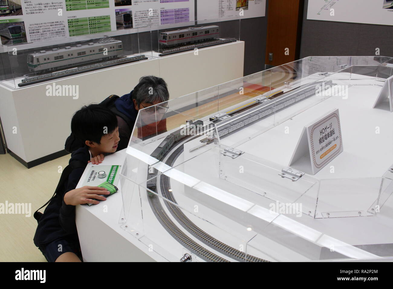 Visitors watch a HO Gauge model of a Chiyoda Line Tokyo Metro train at Tokyo Metro Museum. Some motion blur. - Stock Image