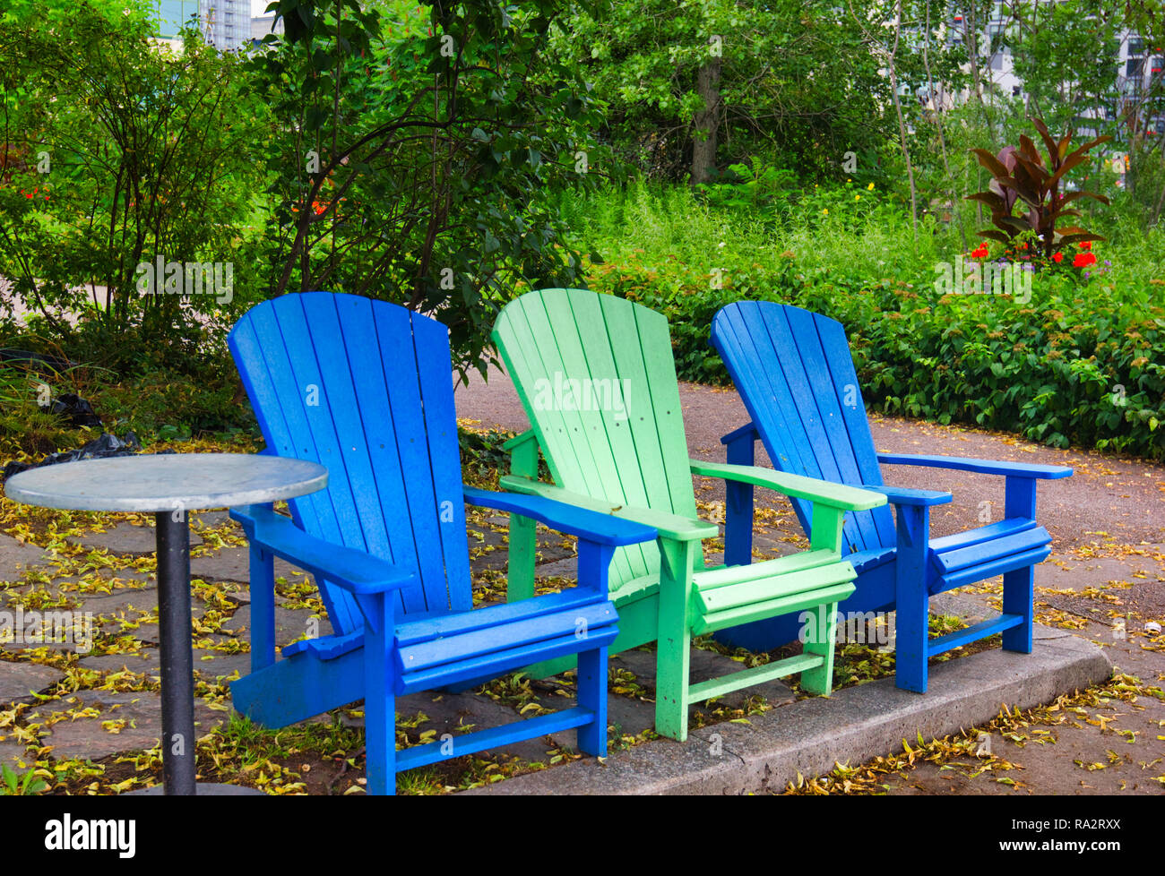 Three empty Adirondack chairs in park, Toronto, Ontario, Canada - Stock Image