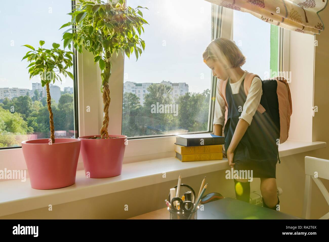 Little girl student with backpack in school uniform looks out the window, background is children's room, desk, computer. School, education, knowledge  Stock Photo