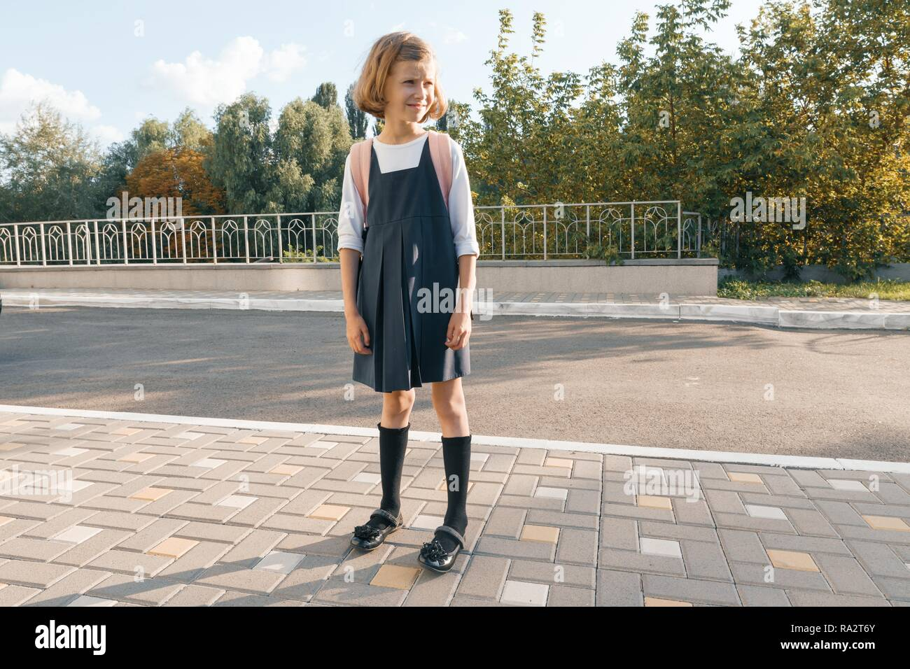Outdoor portrait of a small student, girl with glasses, uniform with backpack. School, education, knowledge and children. - Stock Image