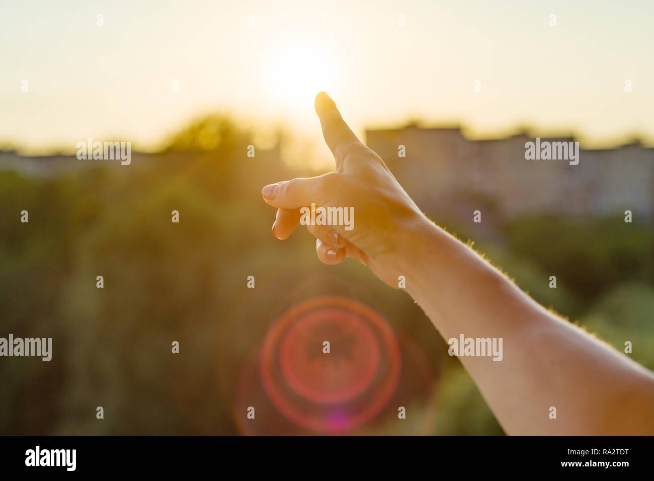 Gesture with the index finger towards the sunset. Background sky, silhouette of the city, sunset. - Stock Image