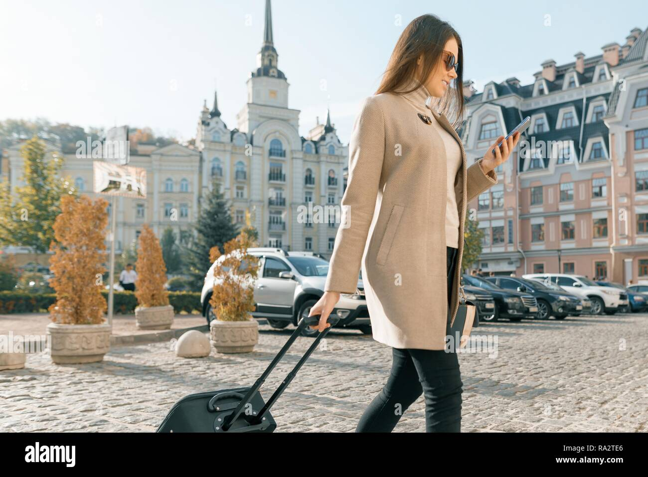 Young beautiful woman walks along city street with travel suitcase and cell phone. Fashionable brunette girl smiling. - Stock Image