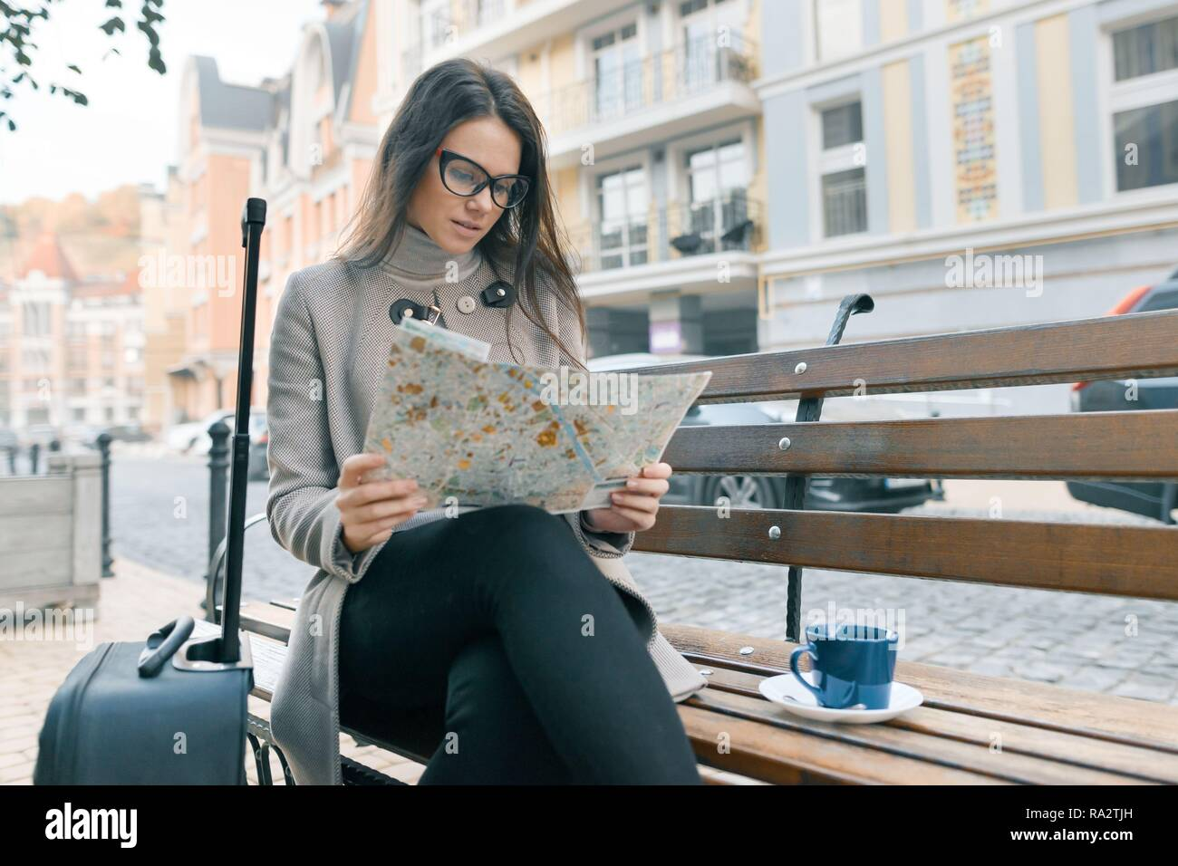 Young beautiful woman sitting on bench with travel suitcase and reading city map, drinks coffee, city street background. - Stock Image