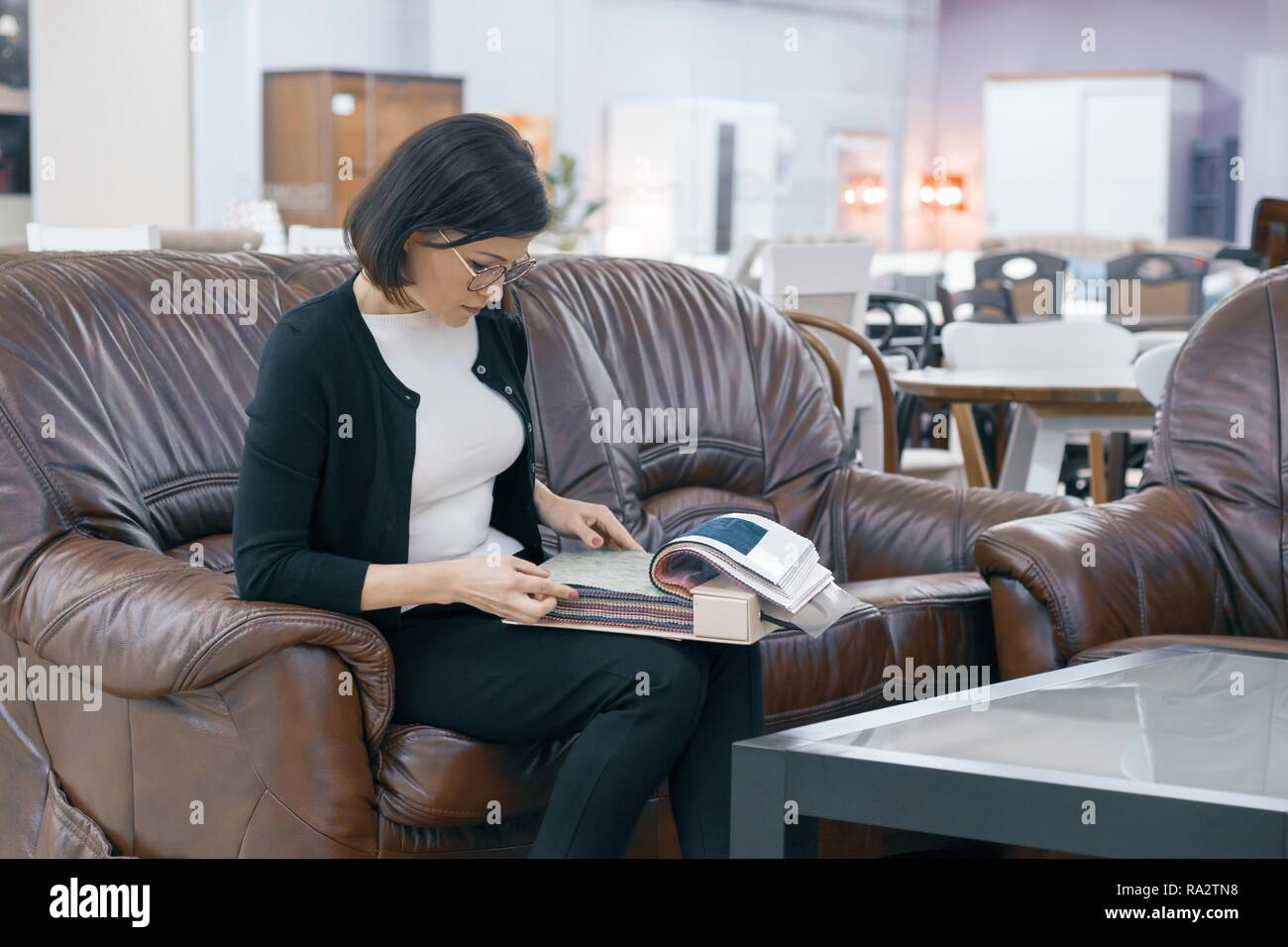 adult woman buyer looking at a book with upholstery fabrics female is sitting on brown