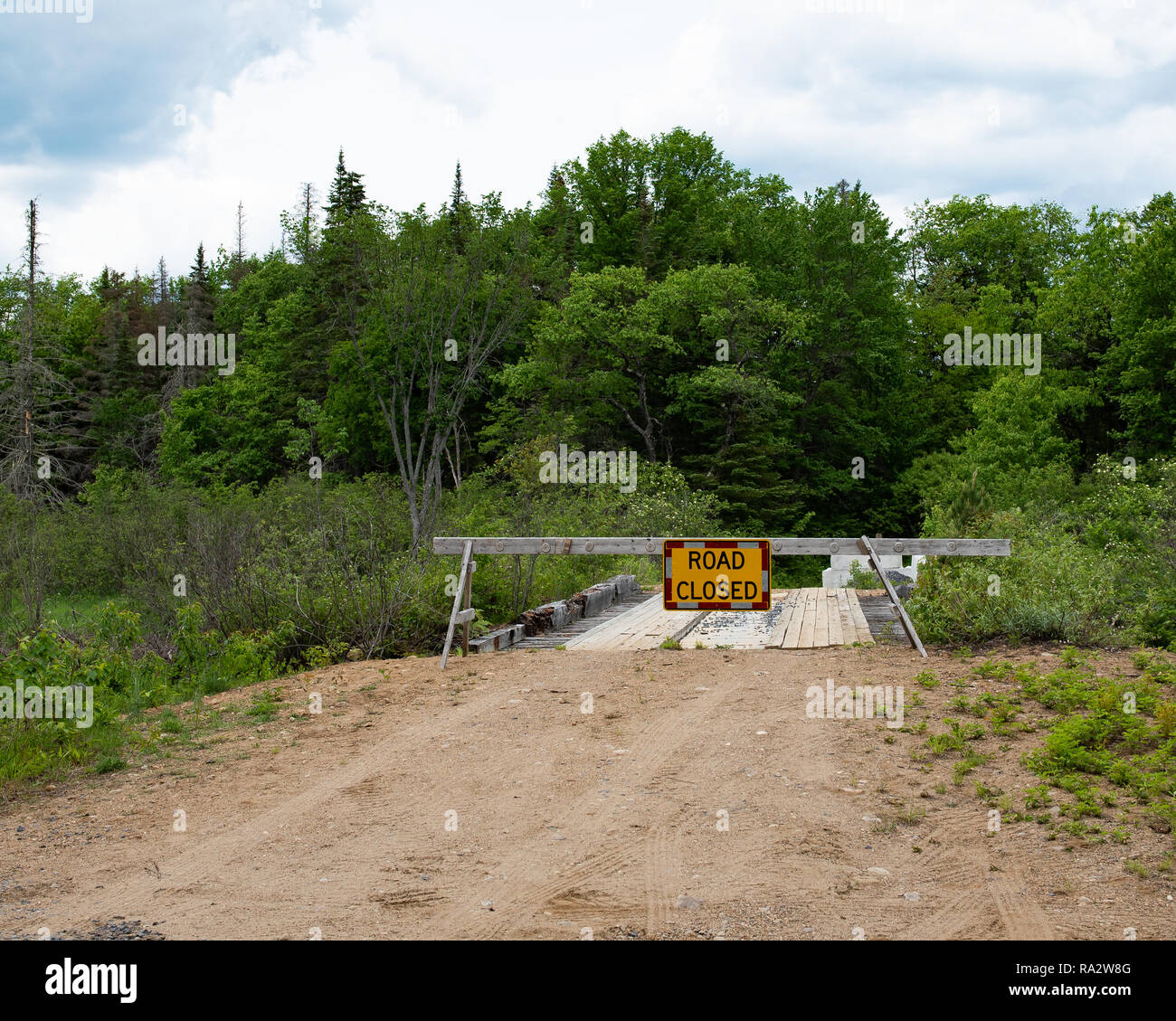 A road closed sign and barricade blocking off a condemned wooden logging bridge in the Adirondack wilderness. - Stock Image