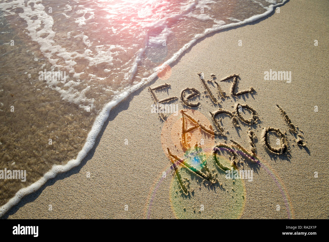 Portuguese Feliz Ano Novo (Happy New Year) message handwritten in textured lettering on smooth sand with a fresh new wave on a Brazilian beach - Stock Image