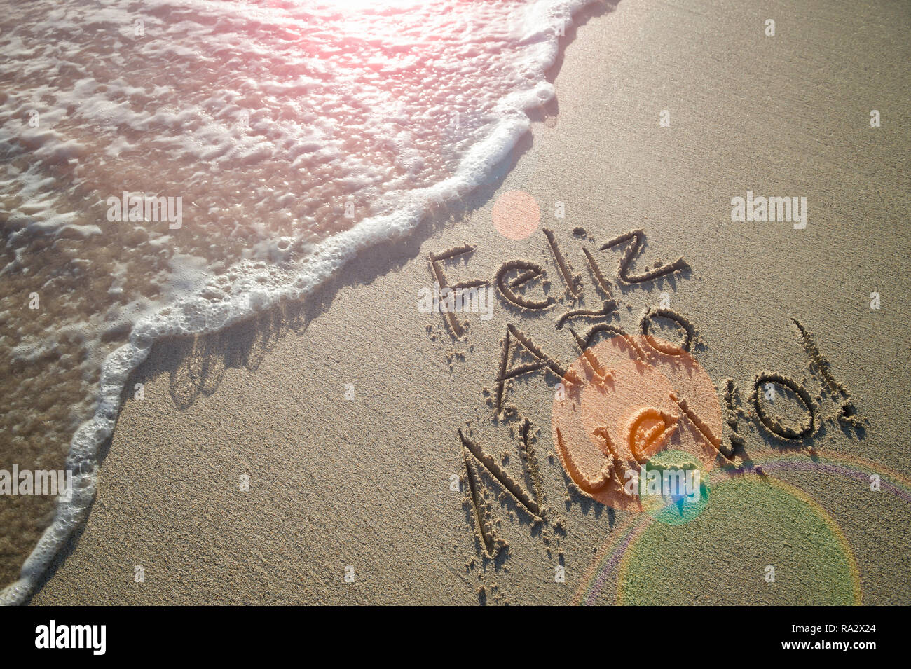 Spanish Happy New Year message (Feliz Año Nuevo) handwritten with textured lettering on smooth sand beach with lens flare above oncoming wave - Stock Image