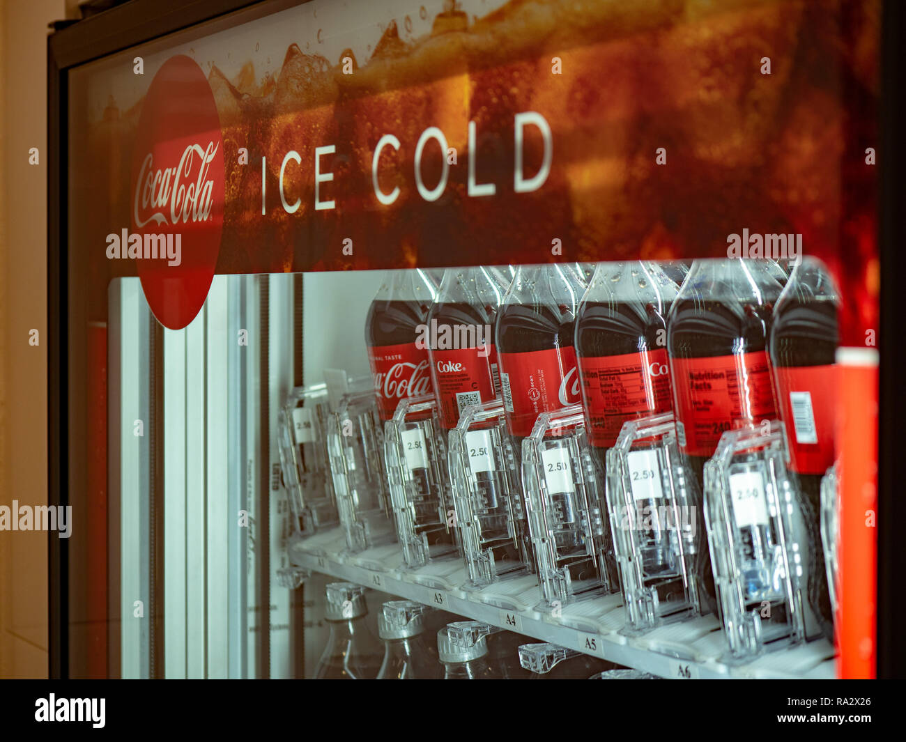 Coca Cola ice cold logo filled with bottles inside a vending machine - Stock Image