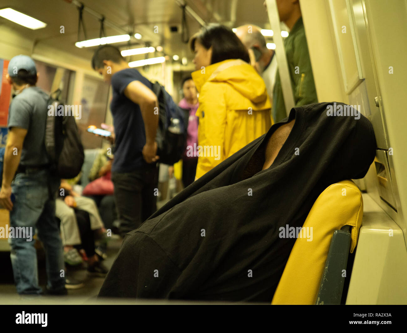 Man sleeps with shirt over his head on a crowded BART subway car - Stock Image