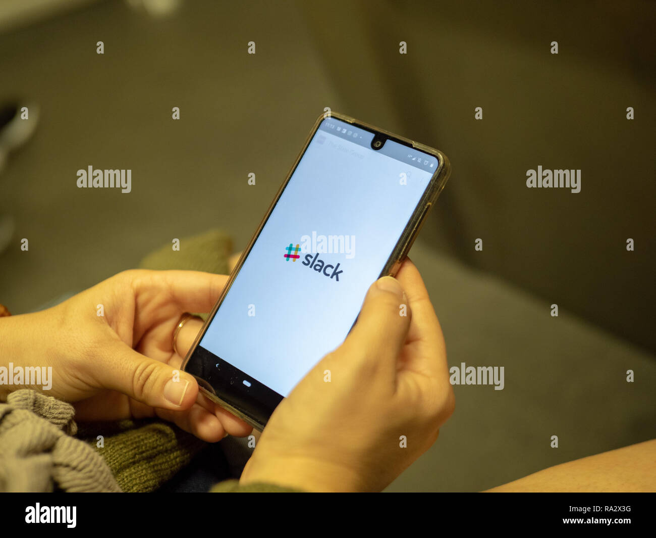 Woman opening Slack mobile communication app with logo on Android screen while commuting on subway train - Stock Image