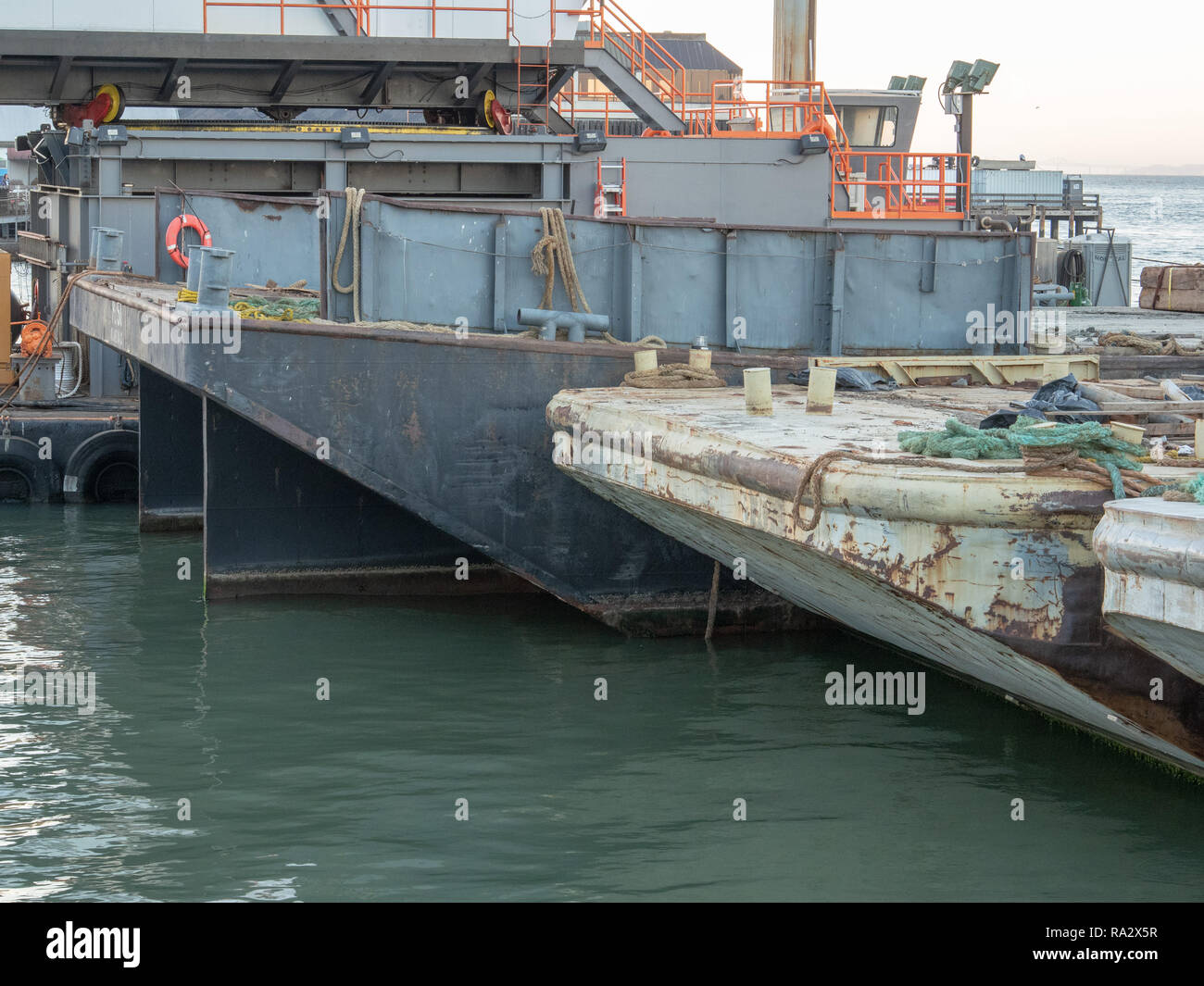Rusty cargo ships and boats among equipment sitting at industrial dock - Stock Image