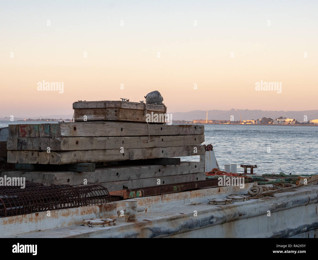Wooden pallets and building materials sitting on a cargo ship overlooking body of water and shoreline - Stock Image