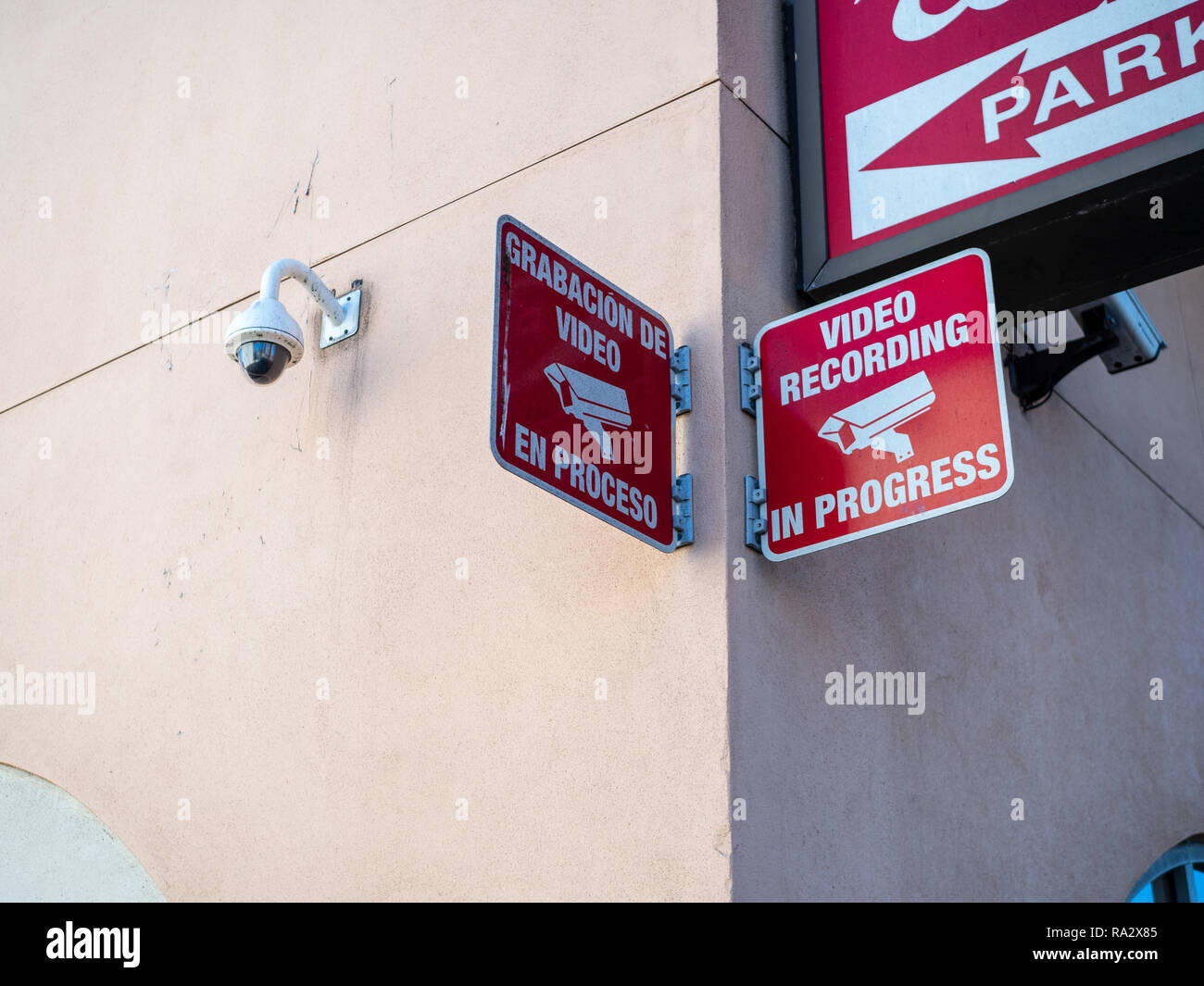 Video recording in progress with surveillance logo along with camera outside of shopping center parking lot - Stock Image