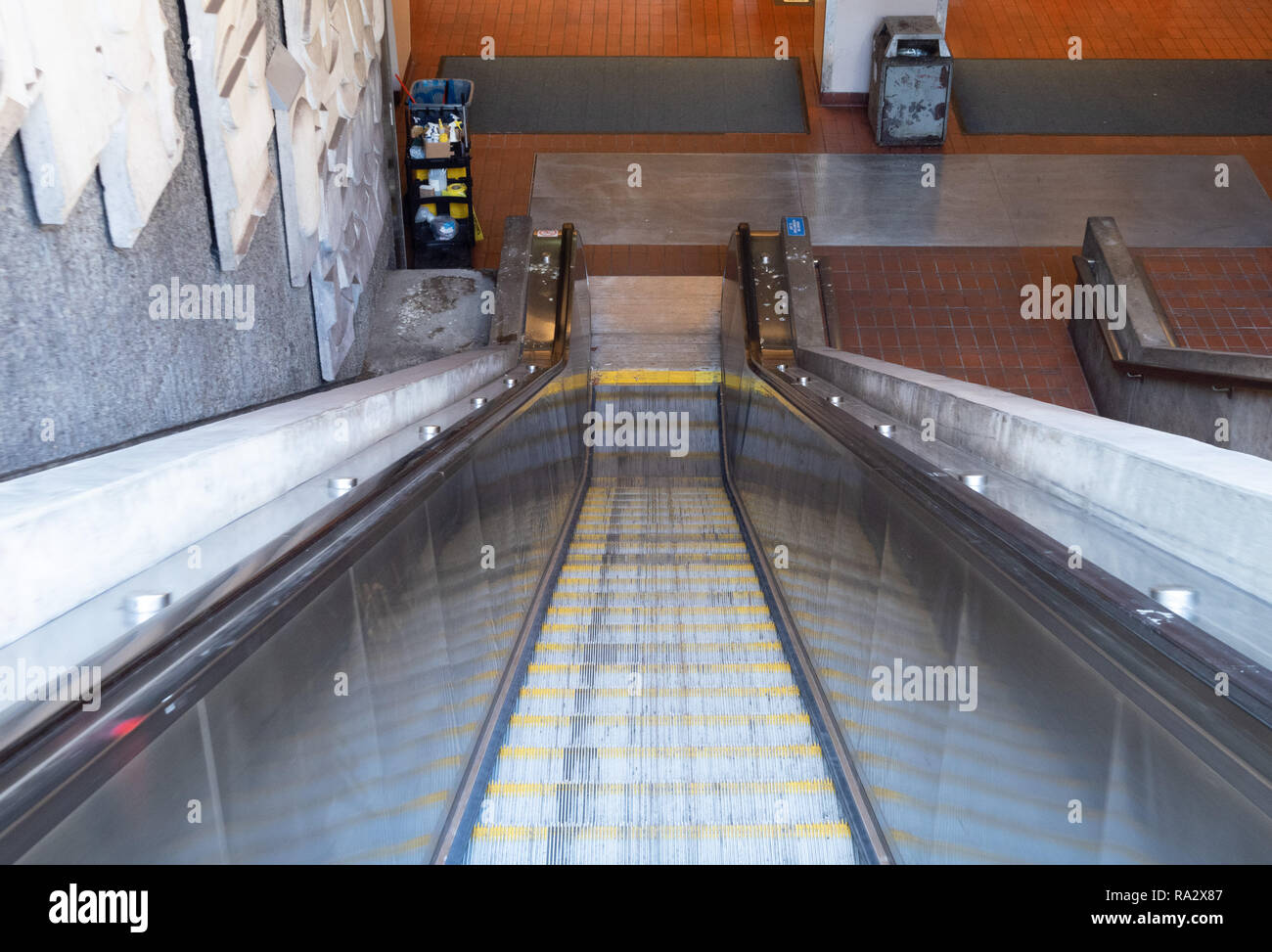 Escalator leading down into a subway tunnel in the daytime - Stock Image