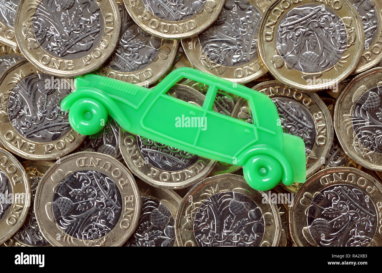 TOY CAR WITH BRITISH ONE POUND COINS RE MOTORING COSTS INSURANCE CAR BUYING SERVICING PRICES  ETC - Stock Image