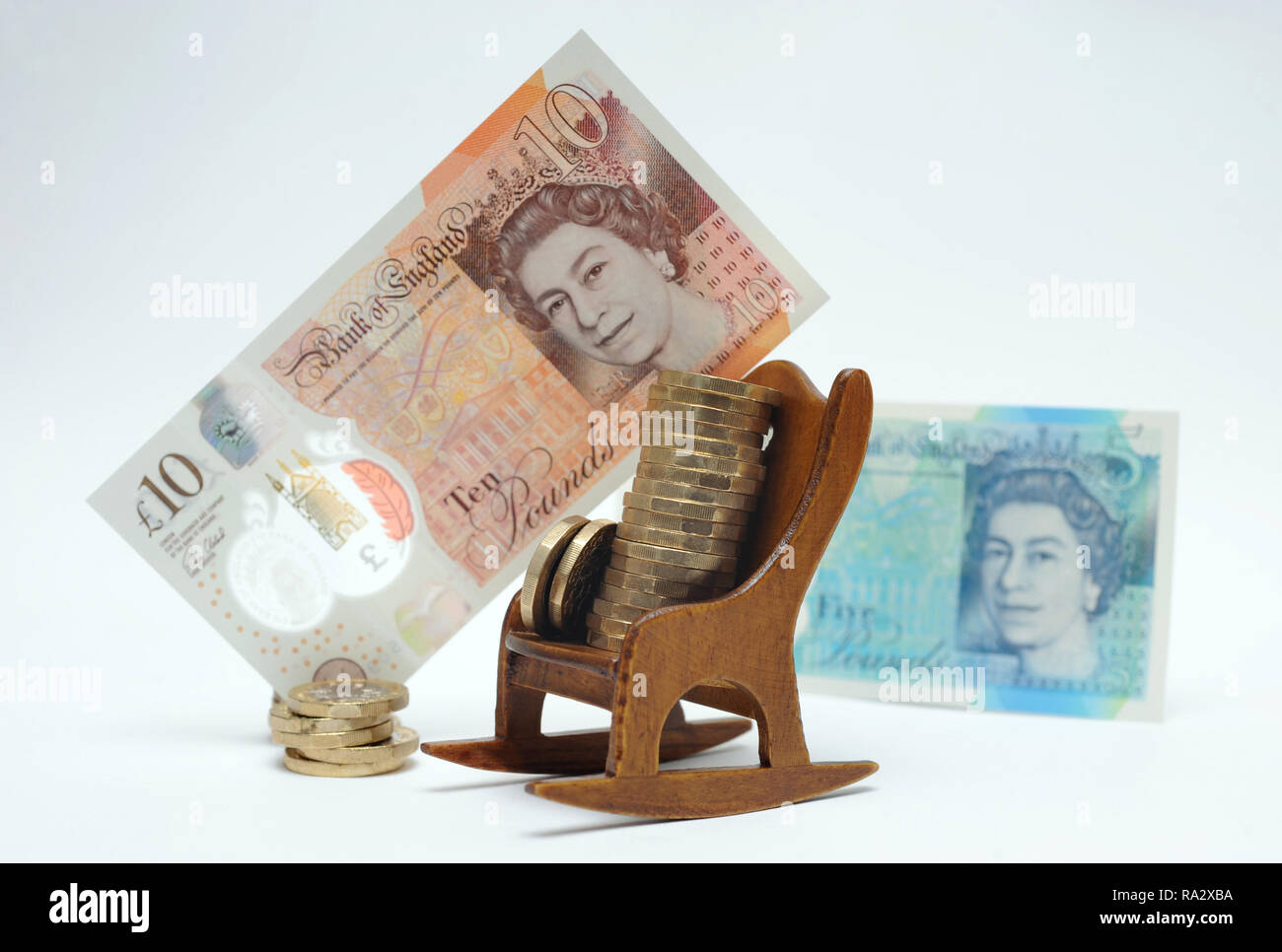 ROCKING CHAIR WITH ONE POUND COINS AND BANKNOTES RE SAVINGS RETIREMENT INVESTMENTS PENSIONERS OLD AGE FINANCES ETC UK - Stock Image