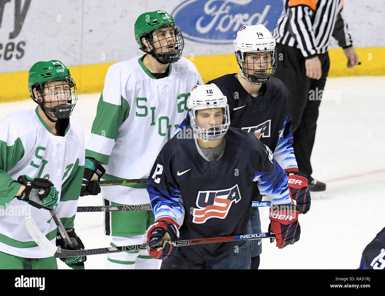 December 29, 2018 North Dakota Fighting Hawks forwards Cole Smith (26) and Jasper Weatherby (14) and U.S. National Under 18 team players Ryder Rolston (12) and Judd Caufield (14) watch the last few seconds tick off the clock during a exhibition men's college hockey game between the U.S. National Under-18 team and the University of North Dakota Fighting Hawks at Ralph Engelstad Arena in Grand Forks, ND. North Dakota was wearing replica 1959 team jerseys. UND won 6-2. Photo by Russell Hons/CSM Stock Photo