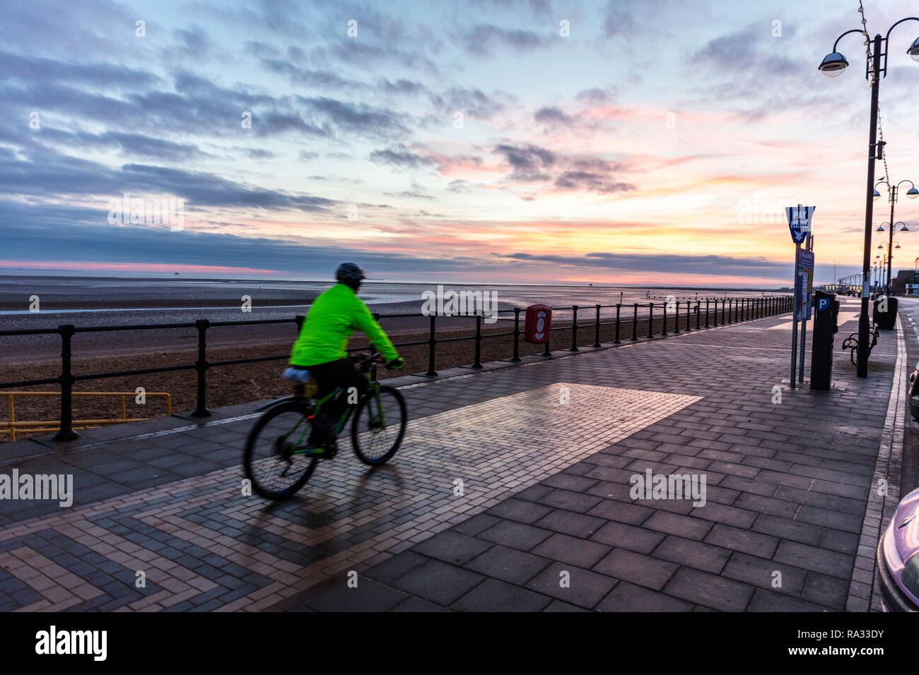 Cleethorpes, Lincolnshire, UK. 31st Dec, 2018. UK Weather: Red sunrise skies in Cleethorpes, Lincolnshire, East Coast, UK. 31st Dec, 2018. Red sky making the perfect backdrop to Cleethorpes Promenade with cyclist starting his new years resolutions early, with partial cloud. Credit: Tommy (Louth)/Alamy Live News - Stock Image